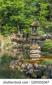 Hisagoike pond, Kaiseki-to lantern and Emerald Waterfall (Midori-taki) at Kenrokuen Garden. Kanazawa City, Ishikawa prefecture, Japan