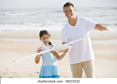 Hispanic 9 year old girl and father playing with toy airplane on beach