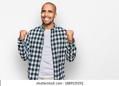 Hispanic adult man wearing casual clothes celebrating surprised and amazed for success with arms raised and open eyes. winner concept.