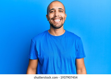 Homme adulte hispanique portant un t-shirt bleu décontracté avec un sourire joyeux et frais au visage. chanceux.