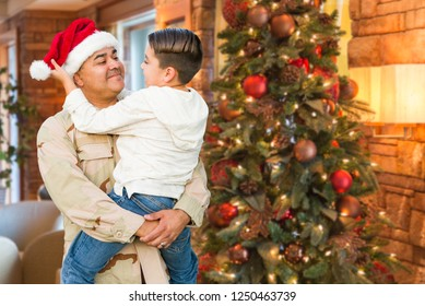 Hispanic Armed Forces Soldier Wearing Santa Hat Hugging Son In Front Christmas Tree.