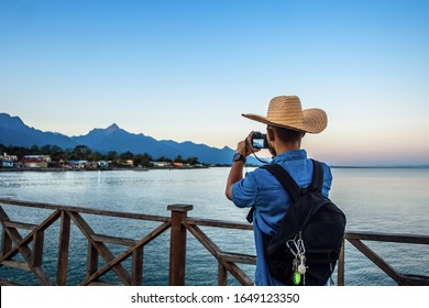 Hispanic with backpack and hat taking a picture with a camera towards the mountain, landscape photography concept, La Ceiba Honduras. - Shutterstock ID 1649123350