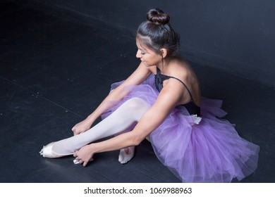 hispanic ballerina putting on pointe shoes backstage