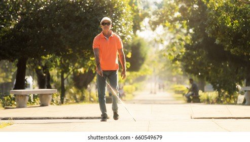 Hispanic blind man, latino people with disability, handicapped person and everyday life. Visually impaired man with walking stick, crossing the street.
