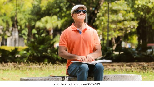 Hispanic blind man, latino people with disability, handicapped person and everyday life. Visually impaired man reading book with hands, touching page written in Braille language with fingers
