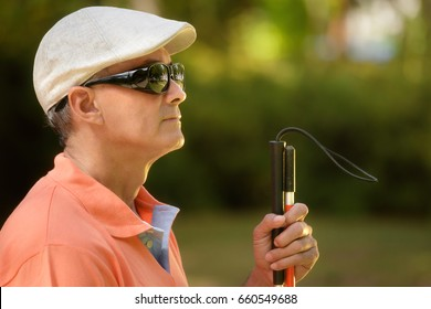 Hispanic blind man, latino people with disability, handicapped person and everyday life. Visually impaired man with walking stick, sitting on bench in city park. Copy space