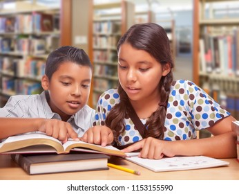 Hispanic Boy and Girl Having Fun Studying Together In The Library.