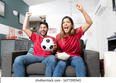 Hispanic boyfriend and girlfriend cheering while watching soccer match at home