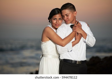 Hispanic bride and groom portrait on orange sunset background with copy space. Young wedding couple hug