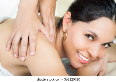 Hispanic brunette model getting massage spa treatment, white towel covering upper body lying horizontal smiling to camera