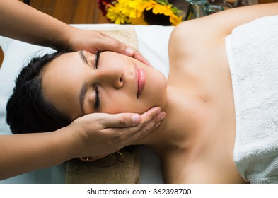 Hispanic brunette model getting massage spa treatment, hands around womans head with eyes closed