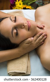 Hispanic brunette model getting massage spa treatment, arms around womans neck with eyes closed