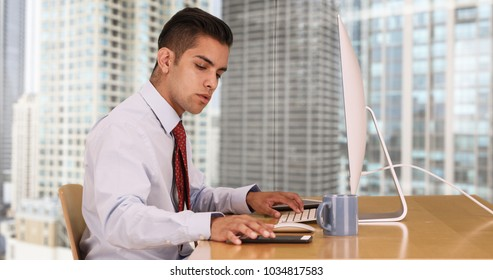 Hispanic business man working on computer while texting on cellphone