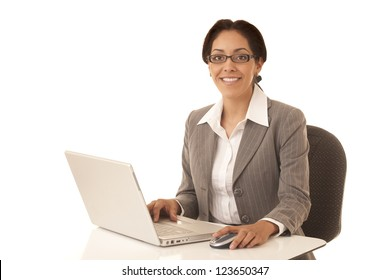 Hispanic business woman sitting at desk working on a laptop computer isolated on white