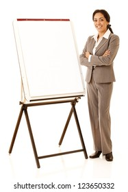 Hispanic business woman wearing business suite standing nest to a presentation easel isolated on white