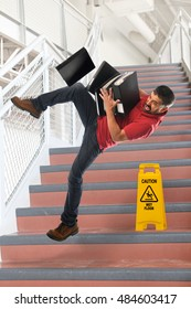 Hispanic businessman falling on stairs while carrying folders