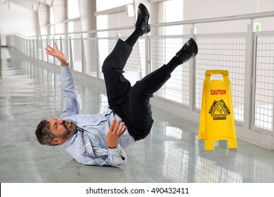 Hispanic businessman falling on wet floor inside office building