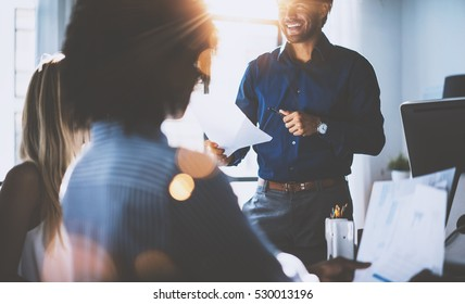 Hispanic businessman holding papers hands and smiling.Young team of coworkers making great business discussion in modern coworking office.Teamwork people concept.Horizontal, blurred background, flares