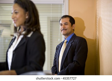 Hispanic businessman looking at young African-American businesswoman in office boardroom