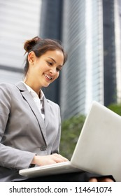 Hispanic Businesswoman Working On Laptop Outside Office