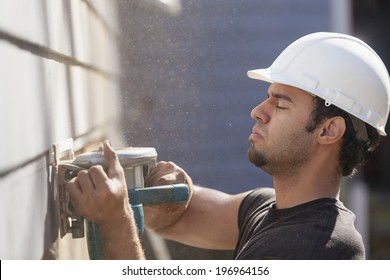 Hispanic carpenter trimming house siding during renovations to add a deck