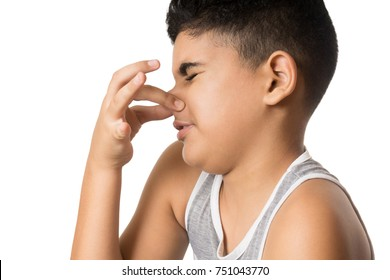 Hispanic child blocks his nose with one hand isolated on white