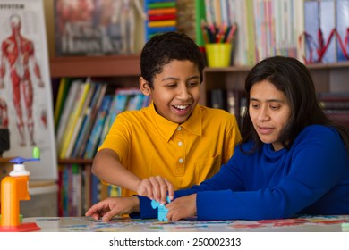Hispanic Child Completing Puzzle with Mom