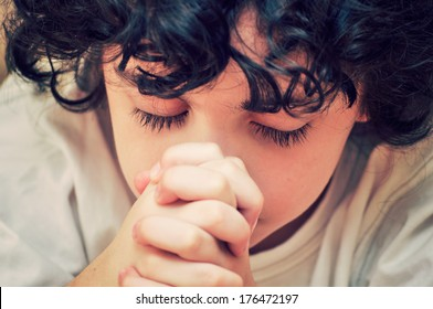 Hispanic child devotedly praying to his Creator in Heaven. Christian worship and relationship. Image has been filtered for effect