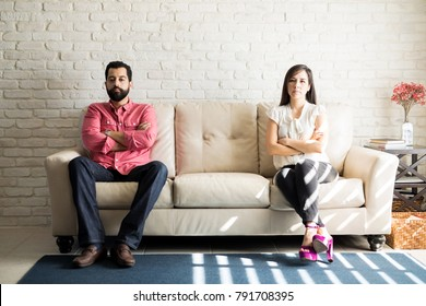 Hispanic couple not talking after a dispute on the sofa at home in the living room