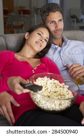 Hispanic Couple On Sofa Watching TV And Eating Popcorn