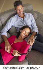 Hispanic Couple On Sofa Watching TV