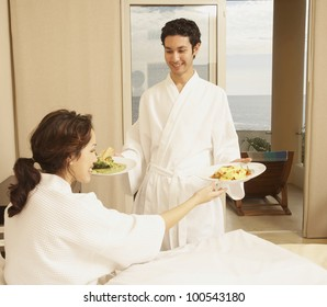 Hispanic couple with plates of food in hotel room