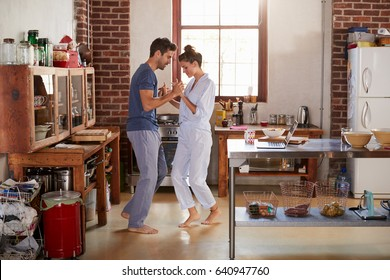 Hispanic couple in pyjamas dancing in kitchen, full length