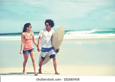 Hispanic couple walk on beach together with surfboard having fun outdoors