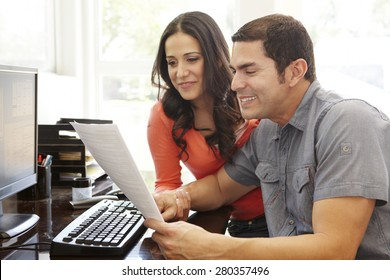 Hispanic couple working in home office