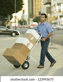 Hispanic delivery man walking on city sidewalk with hand truck full of boxes to deliver
