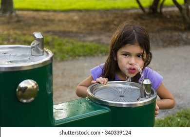 Hispanic elementary aged girl drinking water from a water fountain in park. She is looking at camera.