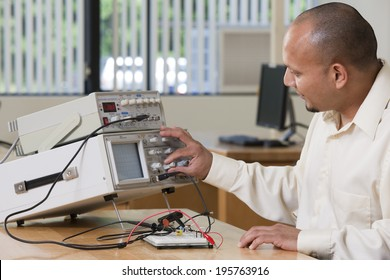 Hispanic engineering student adjusting signal levels of oscilloscope and function generator in college electronics laboratory classroom
