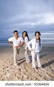 Hispanic family with 9 year old daughter having fun on beach