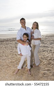 Hispanic family with 9 year old daughter standing on beach