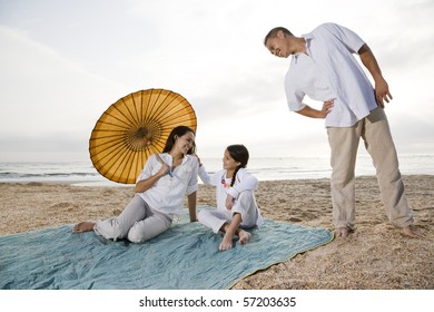 Hispanic family with 9 year old girl on beach blanket