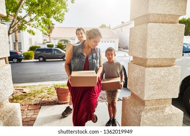 hispanic family carrying boxes into new house