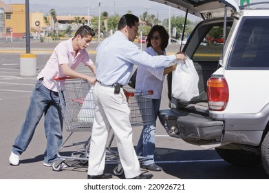 Hispanic family loading groceries into car