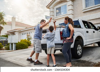 hispanic family loading luggage into back of pickup truck in front of house for travel