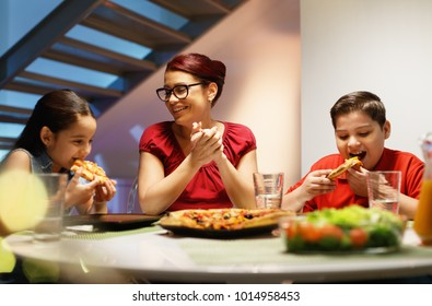 Hispanic family with mom, son and daughter having dinner at home and eating homemade pizza. Latino people with mother, boy and girl during meal. Nutrition, food and lifestyle