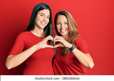 Hispanic family of mother and daughter wearing casual clothes over red background smiling in love doing heart symbol shape with hands. romantic concept.