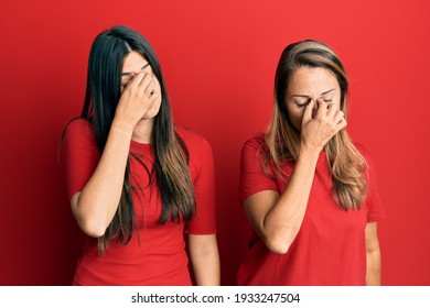 Hispanic family of mother and daughter wearing casual clothes over red background tired rubbing nose and eyes feeling fatigue and headache. stress and frustration concept.