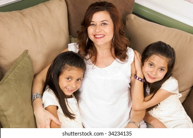 Hispanic family of mother and daughters relaxing on the couch
