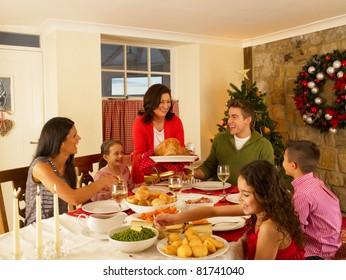 Hispanic family serving Christmas dinner