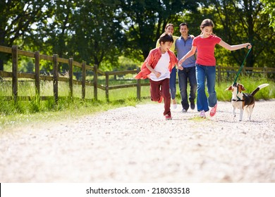 Hispanic Family Taking Dog For Walk In Countryside